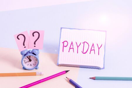 Word writing text Payday. Business photo showcasing a day on which someone is paid or expects to be paid their wages Mini size alarm clock beside stationary placed tilted on pastel backdrop