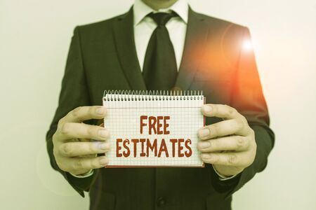 Text sign showing Free Estimates. Business photo showcasing assess an approximate calculation or judgment of the value Male human wear formal work suit office look hold mathematics book use hand Archivio Fotografico