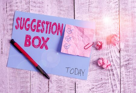 Conceptual hand writing showing Suggestion Box. Concept meaning container which showing can leave comments about something Wrinkle paper and cardboard placed above wooden background Imagens
