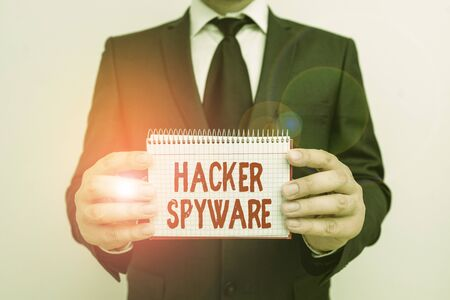 Text sign showing Hacker Spyware. Business photo showcasing infiltration software that secretly monitor unsuspecting user Male human wear formal work suit office look hold mathematics book use hand