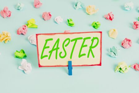 Writing note showing Easter. Business concept for the most important and oldest festival of the Christian Church Colored crumpled papers empty reminder blue floor background clothespin