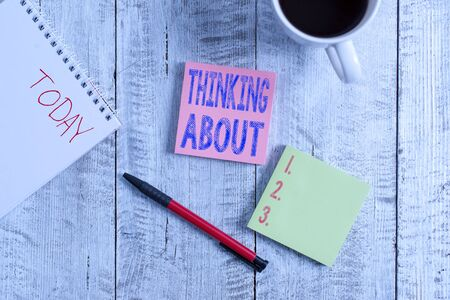 Conceptual hand writing showing Thinking About. Concept meaning means contemplating the situation before you acting Stationary placed next to a coffee cup above wooden table