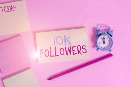 Conceptual hand writing showing 10K Followers. Concept meaning member of the elite group of individuals online Four multicolor notepads marker alarm clock color background Imagens
