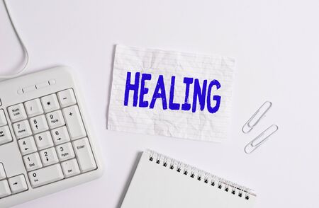 Handwriting text Healing. Conceptual photo process of making or becoming sound or healthy again Helping injured White pc keyboard with empty note paper above white background