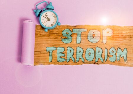 Text sign showing Stop Terrorism. Business photo showcasing Resolving the outstanding issues related to violence Alarm clock and torn cardboard placed above a wooden classic table backdrop Banque d'images