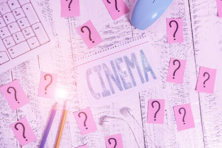 Word writing text Cinema. Business photo showcasing theater where movies are shown for public entertainment Movie theater Writing tools, computer stuff and math book sheet on top of wooden table