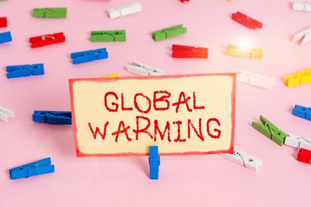 Handwriting text Global Warming. Conceptual photo gradual increase in the temperature of the earth s is atmosphere Colored clothespin papers empty reminder pink floor background office pin