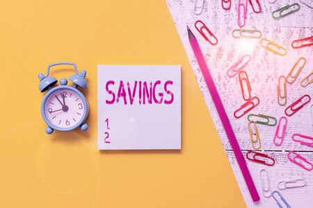 Word writing text Savings. Business photo showcasing the money that a demonstrating keeps in an account in a bank or like Notepad marker pen colored paper sheet clips alarm clock wooden background Archivio Fotografico