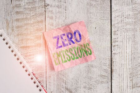 Conceptual hand writing showing Zero Emissions. Concept meaning emits no waste products that pollute the environment Wrinkle note paper and notebook placed on wooden background