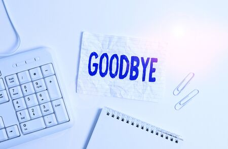 Handwriting text Goodbye. Conceptual photo used to express good wishes when parting or end of a conversation White pc keyboard with empty note paper above white background