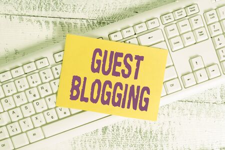 Handwriting text Guest Blogging. Conceptual photo used by the owners of blogs to increase traffic to their site White keyboard office supplies empty rectangle shaped paper reminder wood Stock Photo
