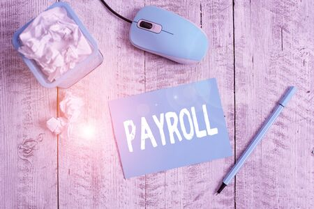Text sign showing Payroll. Business photo showcasing Total amount of money company pays to employees Salary Payment Crumpled paper in bin and computer mouse with stationary on wooden backdrop Reklamní fotografie