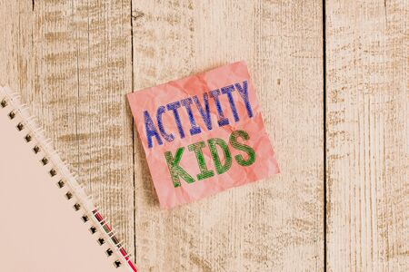 Conceptual hand writing showing Activity Kids. Concept meaning form of organized supervised often extracurricular recreation Wrinkle note paper and notebook placed on wooden background