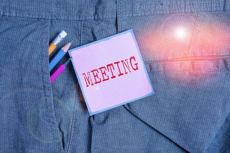 Handwriting text writing Meeting. Conceptual photo assembly of showing for a particular purpose or for formal discussion Writing equipment and pink note paper inside pocket of man work trousers