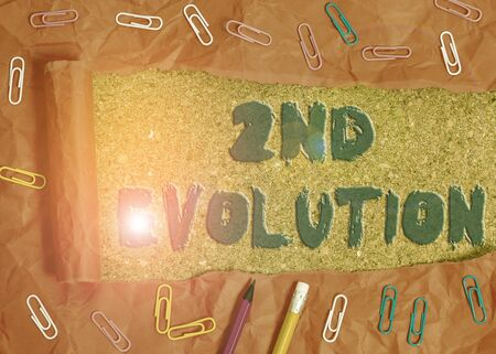 Writing note showing 2Nd Evolution. Business concept for change in the heritable features of biological populations Stationary and torn cardboard on a wooden classic table backdrop