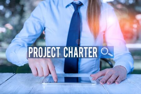 Writing note showing Project Charter. Business concept for typically short formal document that describes your project Female business person sitting by table and holding mobile phone Imagens