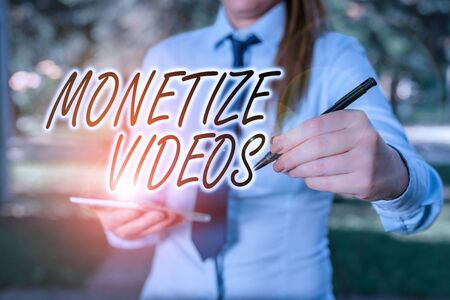 Handwriting text writing Monetize Videos. Conceptual photo process of earning money from your uploaded YouTube videos Woman in a blue business shirts pointing with her finger into empty space Stockfoto