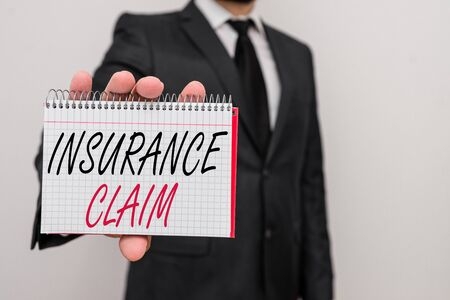 Text sign showing Insurance Claim. Business photo text coverage or compensation for a covered loss or policy event Male human wear formal work suit office look hold mathematics book use hand