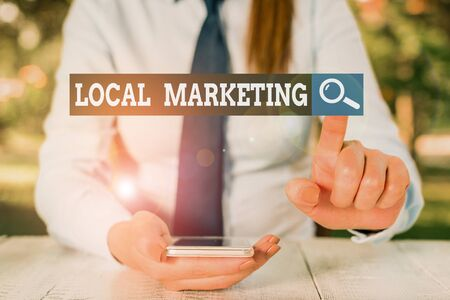 Text sign showing Local Marketing. Business photo showcasing targets customers by finely grained location such as a city Female business person sitting by table and holding mobile phone Stock Photo