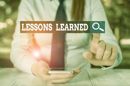 Text sign showing Lessons Learned. Business photo showcasing the knowledge or understanding gained by experience Female business person sitting by table and holding mobile phone
