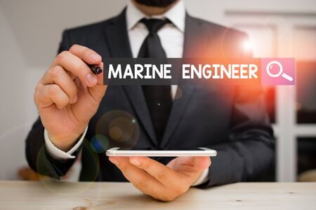 Conceptual hand writing showing Marine Engineer. Concept meaning incharge with maintenance and operation of a ship s is engines Male human wear formal clothes present use hitech smartphone