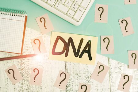 Conceptual hand writing showing Dna. Concept meaning a selfreplicating material wpresent in nearly all living organisms Writing tools and scribbled paper on top of the wooden table