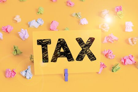 Text sign showing Tax. Business photo text Compulsory contribution to state revenue Levy impose by government Colored crumpled papers empty reminder white floor background clothespin