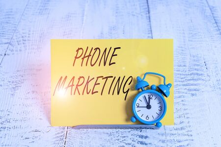 Writing note showing Phone Marketing. Business concept for art of promoting products and services via mobile devices Alarm clock tilted above buffer wire in front of notepaper