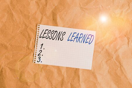 Text sign showing Lessons Learned. Business photo showcasing the knowledge or understanding gained by experience Papercraft craft paper desk square spiral notebook office study supplies Stock Photo