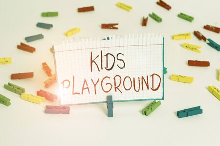 Text sign showing Kids Playground. Business photo showcasing piece of land designed for children to play in outside Colored clothespin papers empty reminder white floor background office Stock Photo