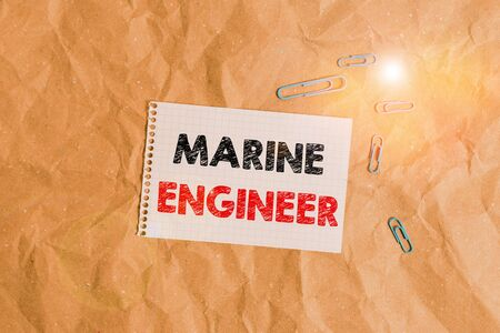 Conceptual hand writing showing Marine Engineer. Concept meaning incharge with maintenance and operation of a ship s is engines Papercraft desk square spiral notebook office study supplies Standard-Bild