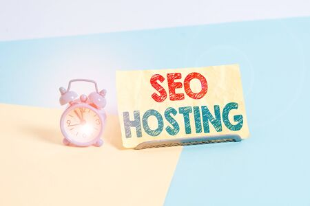 Writing note showing Seo Hosting. Business concept for building website in a way that is friendly for search engines Alarm clock beside a Paper sheet placed on pastel backdrop