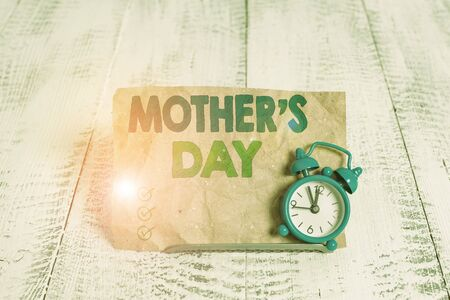Handwriting text writing Mother S Day. Conceptual photo a celebration honoring the mother of the family or motherhood Mini blue alarm clock stand tilted above buffer wire in front of notepaper