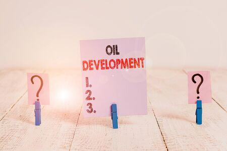 Conceptual hand writing showing Oil Development. Concept meaning act or process of exploring an area on land or sea for oil Crumbling sheet with paper clips placed on the wooden table Stock fotó