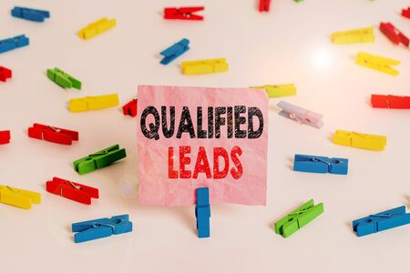 Conceptual hand writing showing Qualified Leads. Concept meaning lead judged likely to become a customer compared to other Colored clothespin papers empty reminder white floor office