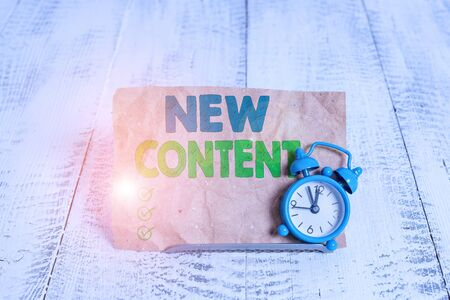 Handwriting text writing New Content. Conceptual photo fresh valuable and relevant information or context of a document Mini blue alarm clock stand tilted above buffer wire in front of notepaper
