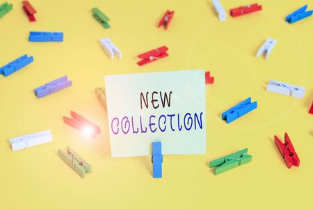 Writing note showing New Collection. Business concept for Latest fashion trend Updated designed for the next season Colored clothespin papers empty reminder yellow floor background office Archivio Fotografico