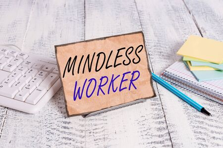 Conceptual hand writing showing Mindless Worker. Concept meaning Having no intelligent purpose Showing little attention Notepaper on wire in between computer keyboard and sheets