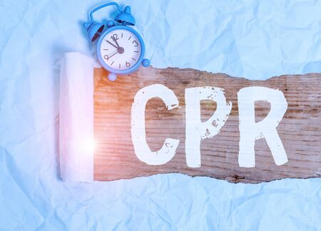 Word writing text Cpr. Business photo showcasing cardiopulmonary resuscitation Method used to keep someone alive Alarm clock and torn cardboard placed above a wooden classic table backdrop Stok Fotoğraf