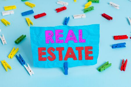 Word writing text Real Estate. Business photo showcasing the property consisting of land and the buildings on it Colored clothespin papers empty reminder blue floor background office pin