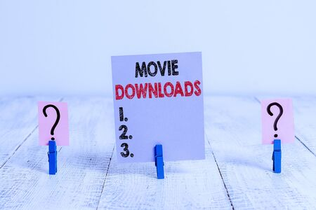 Conceptual hand writing showing Movie Downloads. Concept meaning transfers entire film for local storage and later use Crumbling sheet with paper clips placed on the wooden table Stockfoto