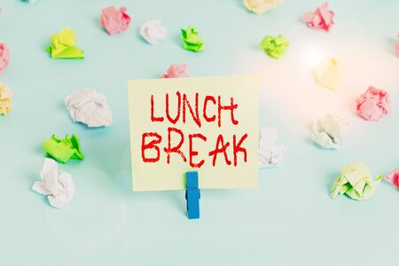 Word writing text Lunch Break. Business photo showcasing time when a demonstrating stops working or studying to have lunch Colored crumpled papers empty reminder blue floor background clothespin