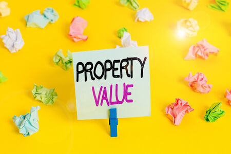 Writing note showing Property Value. Business concept for refers to the fair market value of a given piece of property Colored crumpled paper empty reminder white floor clothespin