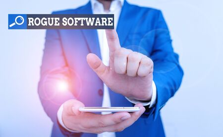 Conceptual hand writing showing Rogue Software. Concept meaning type of malware that poses as antimalware software Businessman in the blue suite with lap top pointing with finger
