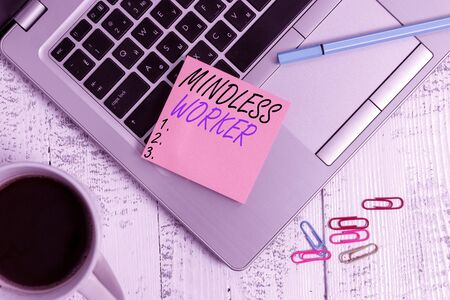 Word writing text Mindless Worker. Business photo showcasing Having no intelligent purpose Showing little attention Trendy metallic laptop blank sticky pad coffee cup clips pen vintage table Stok Fotoğraf