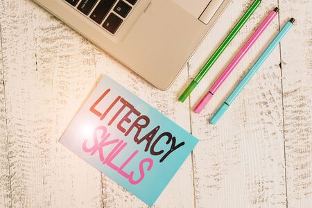 Handwriting text writing Literacy Skills. Conceptual photo all knowledge and skills need to evaluate information Trendy metallic laptop blank sticky pad three pens lying vintage table Standard-Bild