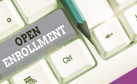 Writing note showing Open Enrollment. Business concept for policy of allowing qualifying students to enroll in school Фото со стока
