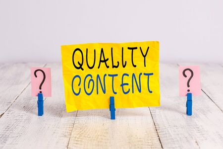 Writing note showing Quality Content. Business concept for content that delivers value and consists of great writing Crumbling sheet with paper clips placed on the wooden table