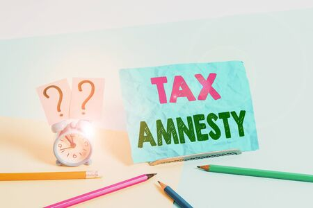 Word writing text Tax Amnesty. Business photo showcasing limitedtime opportunity for specified group of taxpayers to pay Mini size alarm clock beside stationary placed tilted on pastel backdrop