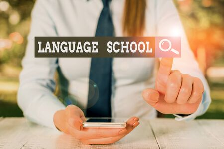 Text sign showing Language School. Business photo showcasing educational institution where foreign languages are taught Female business person sitting by table and holding mobile phone